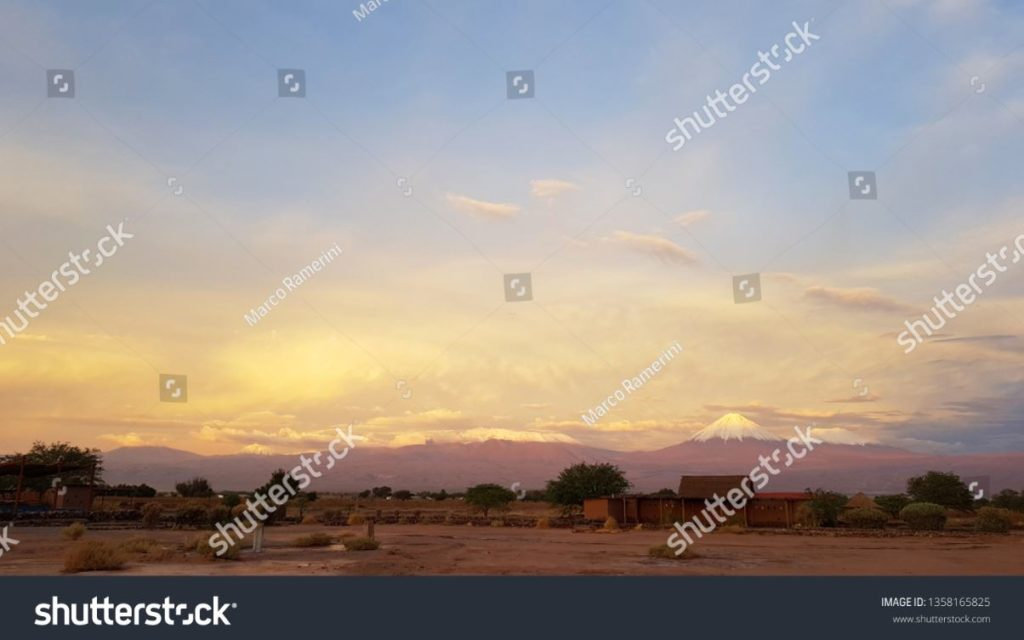 Sunset lights in the arid and desolate landscape of the Atacama desert with the tops of the snowy volcanoes of the Andes mountain range in the background. Author and Copyright Marco Ramerini